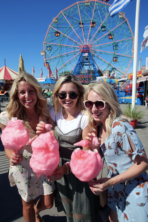 Bloggers Lauren Wells Jessica Sturdy Cambria Grace with cotton candy in front of the ferris wheel at Coney Island in NYC