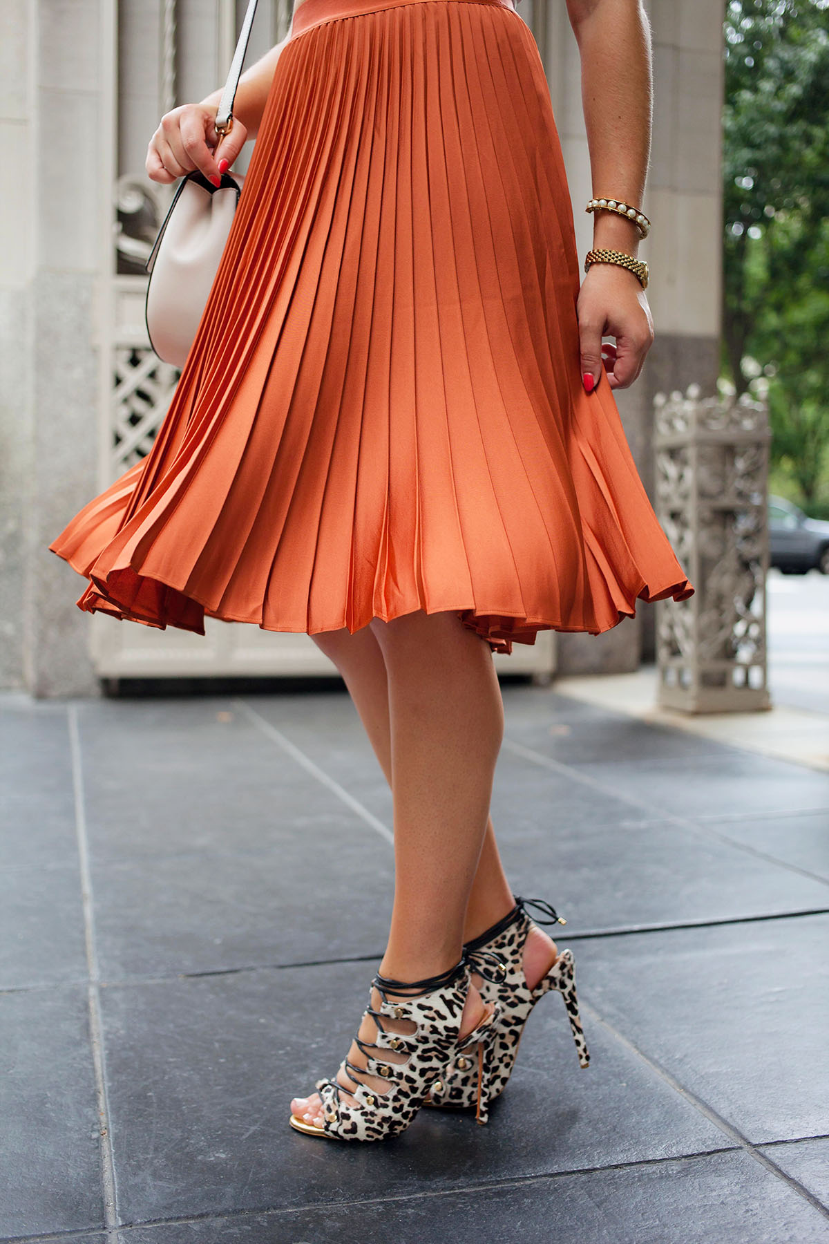 Pleated skirts are one of fall's hottest trends! Blogger Bows & Sequins styles her rust-colored skirt with lace-up leopard heels and a round crossbody bag.