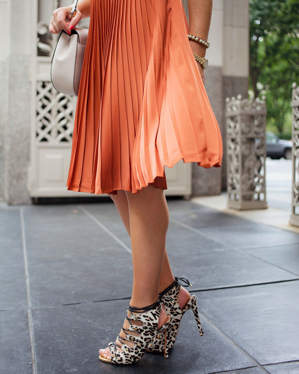 Pleated skirts are one of fall's hottest trends! Blogger Bows & Sequins styles her burnt orange skirt with lace-up leopard heels and a round crossbody bag.