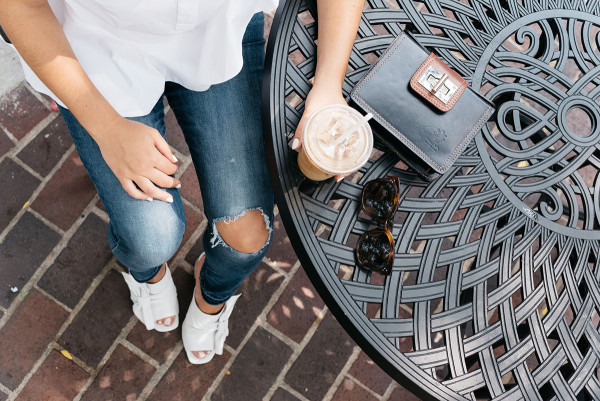 Lifestyle blogger Bows & Sequins at Bow Truss Coffee Shop in Mariano Park in Chicago's Gold Coast. She's wearing a white blouse, ripped jeans, white leather heels, and Celine sunglasses.