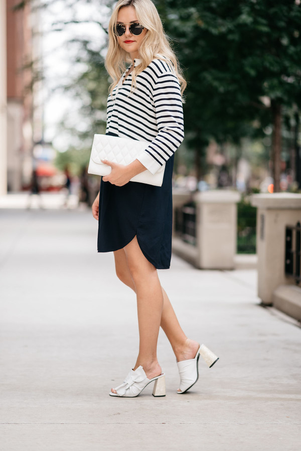Jessica Sturdy of Bows & Sequins, a fashion-focused lifestyle blog, wearing a striped shirtdress, white clutch purse, Topshop bow shoes, and sunglasses in Chicago's Gold Coast.