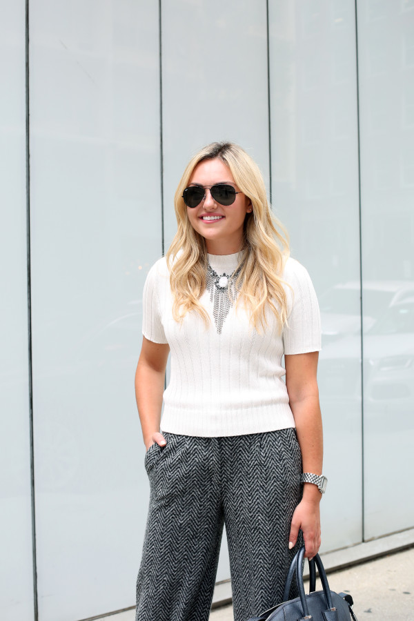 Bows & Sequins styling a monochromatic fall work outfit with a short sleeve sweater, statement necklace, and wool pants.