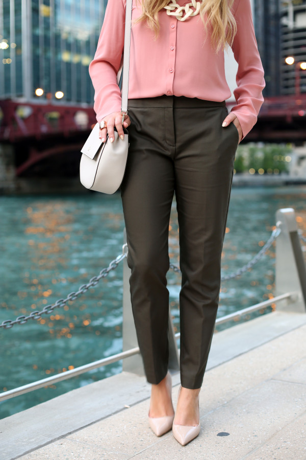 Bows & Sequins styling a pair of slim-fit ankle length pants for work. A silky pink blouse, olive green pants, nude pointed toe pumps, and a cream-colored crossbody bag.