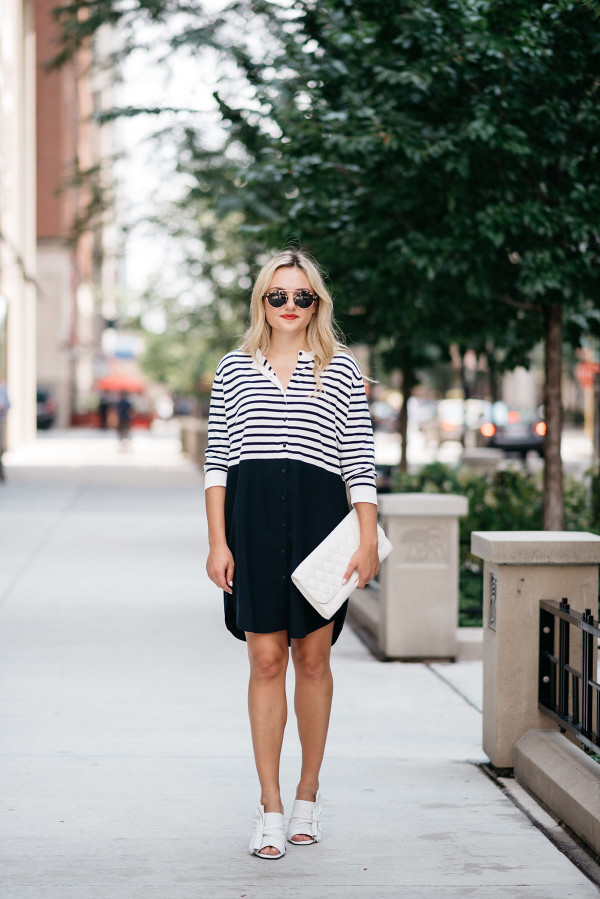 Bows & Sequins, a fashion-focused lifestyle blog, wearing a striped shirtdress, Vera Bradley white clutch purse, sunglasses, and white bow shoes.