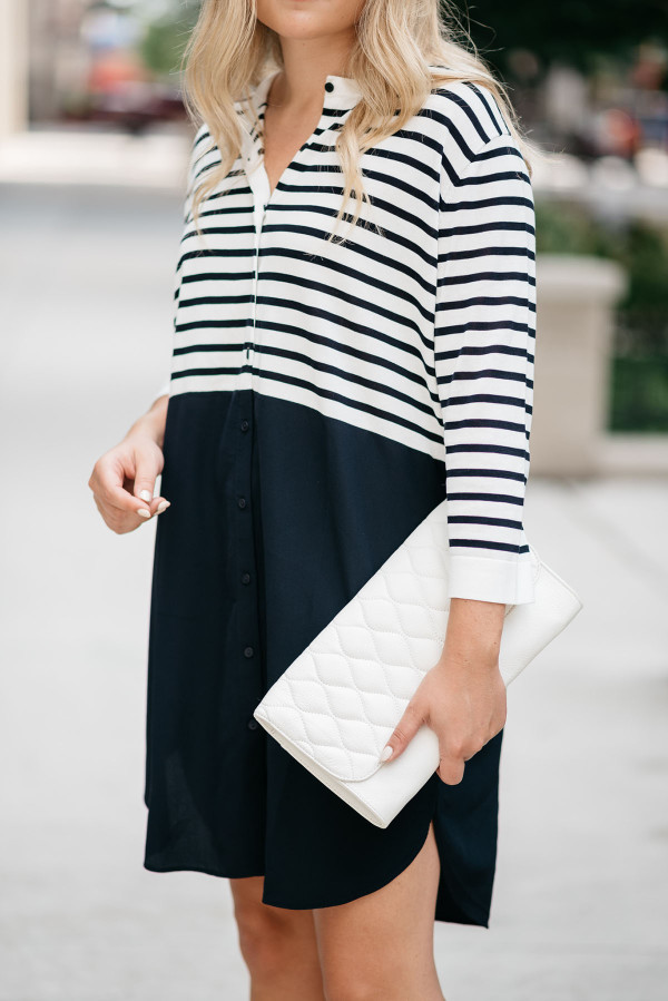 Jessica Sturdy of Bows & Sequins, a fashion-focused lifestyle blog, styles a Vera Bradley white clutch purse with a striped t-shirt dress.