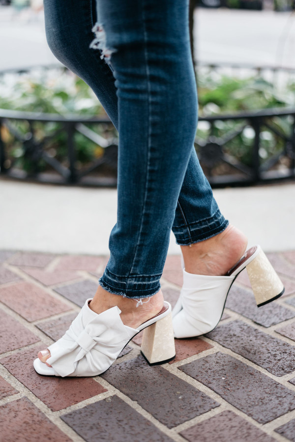 Bows & Sequins styling a pair of distressed hem jeans and leather bow mules with a pearl heel.