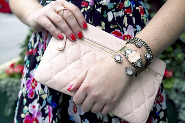 Style blogger Bows & Sequins styling a blush leather clutch purse with Loren Hope bracelets in London.