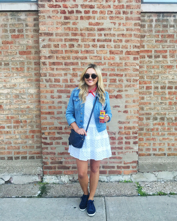 Bows & Sequins at North Coast Music Festival in Chicago wearing a white eyelet dress, a denim jacket, navy blue sneakers, and a red bandana.