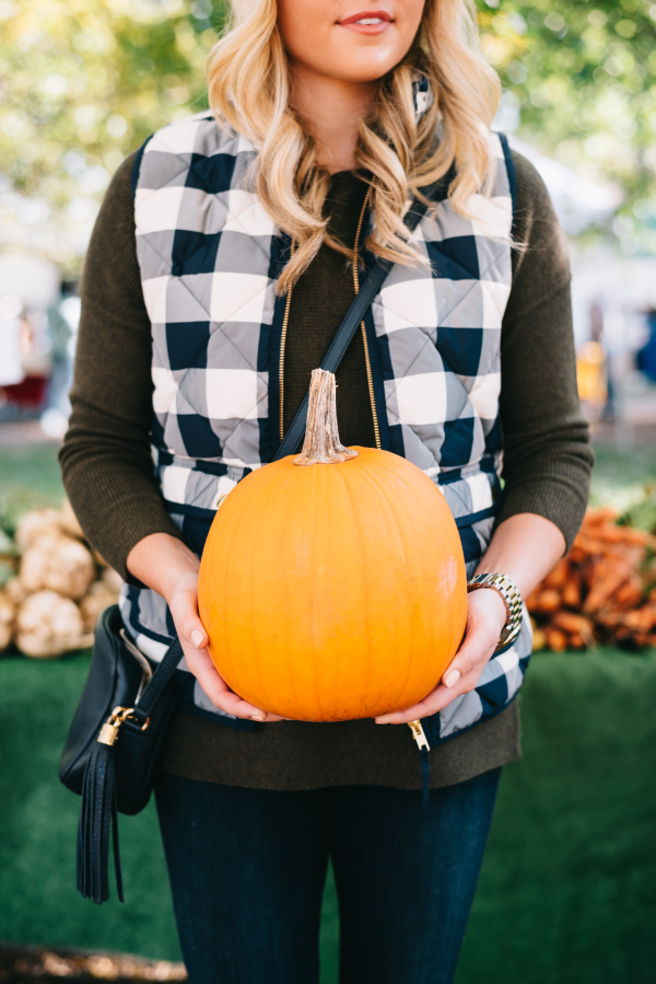 Blogger Bows & Sequins wearing a cute gingham vest and olive green sweater at a pumpkin patch!