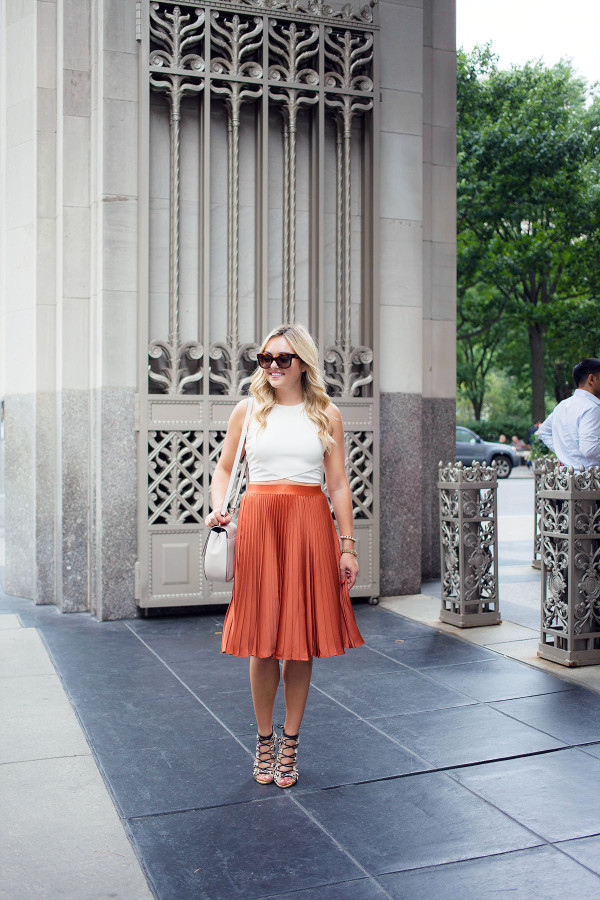 Pleated skirts are one of fall's hottest trends! Blogger Bows & Sequins styles hers with a crop-top tank, lace-up leopard heels, oversized sunglasses, and a round crossbody bag.