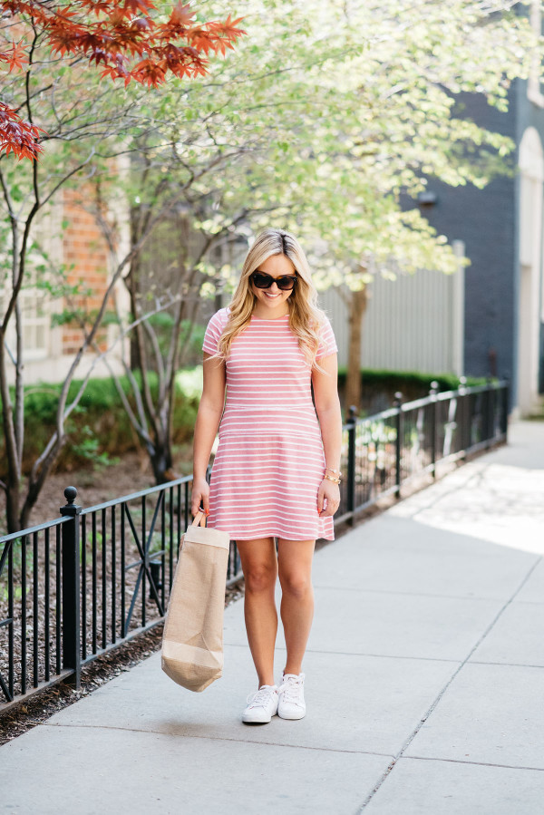 Fashion blogger Bows & Sequins wearing a pink and white striped dress, white Tommy Hilfiger eyelet sneakers, a Apolis Market tote, and sunglasses.