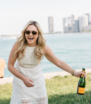 Bows & Sequins wearing a white lace dress and popping Veuve Clicquot champagne along the lakefront in Chicago.