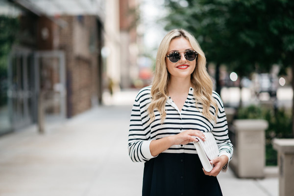 Jessica Sturdy for Bows & Sequins, a fashion-focused lifestyle blog, wearing a striped shirtdress, white clutch, and Illesteva sunglasses.