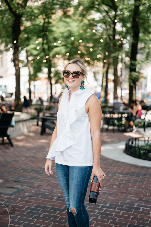 Fashion blogger Bows & Sequins wearing a ruffled sleeveless blouse, statement earrings, and Celine sunglasses in Chicago's Gold Coast at Mariano Park by Bow Truss Coffee Shop.