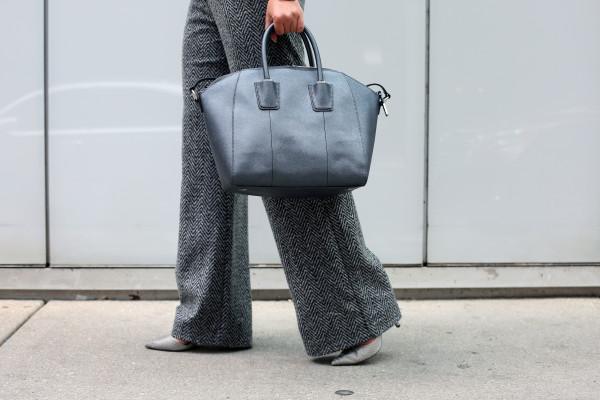 Bows & Sequins wearing a pair of wide-leg work pants, pointed toe pumps, and a metallic leather tote.