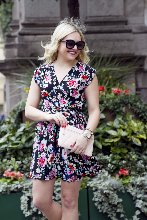 Jessica Sturdy of Bows & Sequins, a fashion-focused lifestyle blog, styling a navy floral wrap dress with a Vera Bradley blush leather clutch purse in London.