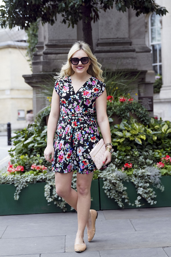 Jessica Sturdy of Bows & Sequins, a fashion-focused lifestyle blog, styling a navy floral dress with a blush leather clutch purse in London.