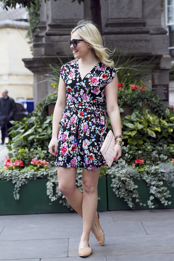 Fashion blogger Bows & Sequins wearing a navy floral Yumi Kim Wrap Dress and Vera Bradley leather clutch in London.