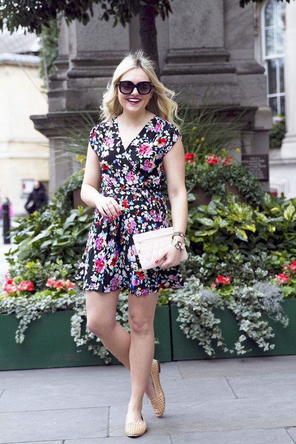 Fashion blogger Bows & Sequins wearing a floral Yumi Kim Wrap Dress and leather clutch in London.