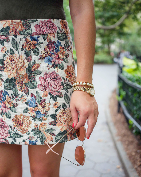 Bows & Sequins wearing an olive green body suit, a woven floral skirt, a Lele Sadoughi pearl cuff, a petite Michael Kors gold bracelet watch, and blush pink sunglasses.