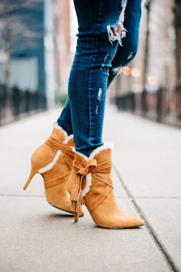 Bows & Sequins wearing a pair of Schutz shearling booties with ripped jeans.