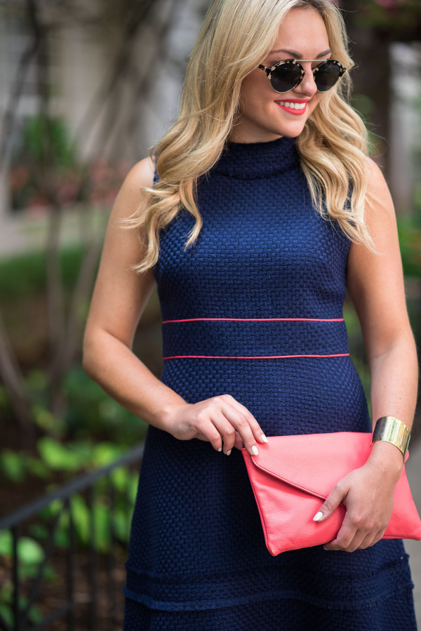 Jessica Sturdy of Bows & Sequins, a fashion-focused lifestyle blog, styling a navy and coral Sail to Sable dress, gold bracelet, and coral purse in Chicago.