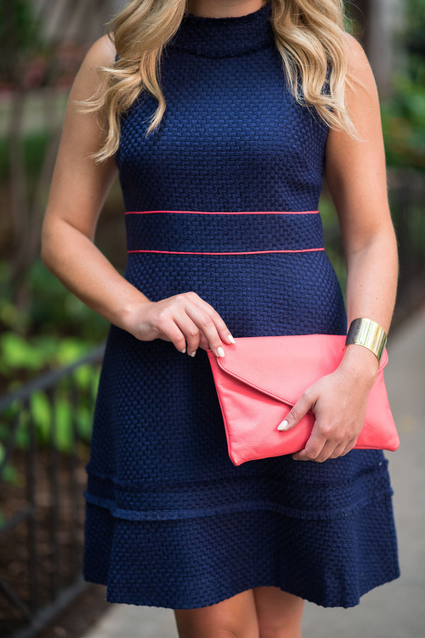Fashion blogger Bows & Sequins styling a Sail to Sable navy blue dress, coral clutch purse, and a gold bracelet in Chicago.