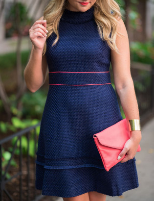 Fashion blogger Jessica Sturdy of Bows & Sequins wearing a navy blue and coral dress, coral clutch bag, and gold bracelet in Chicago.