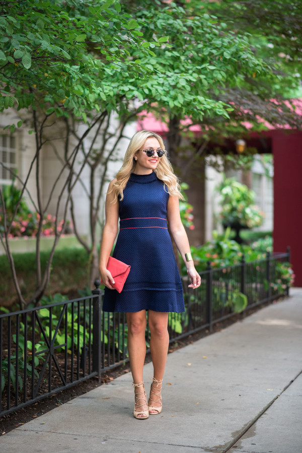 Fashion blogger Bows & Sequins wearing a navy blue and coral dress, sunglasses, and coral clutch in Chicago.