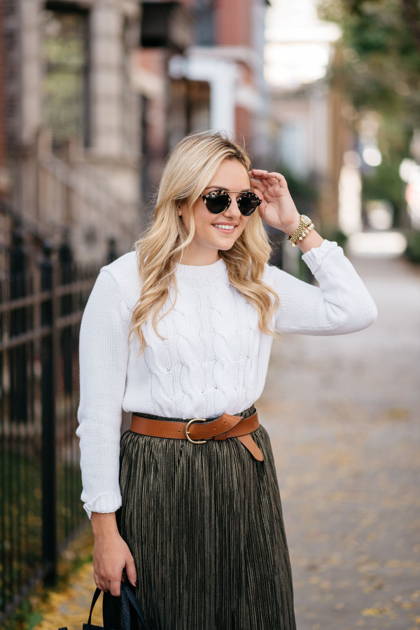 Bows & Sequins wearing a cable knit sweater, leather belt, and pleated metallic skirt.
