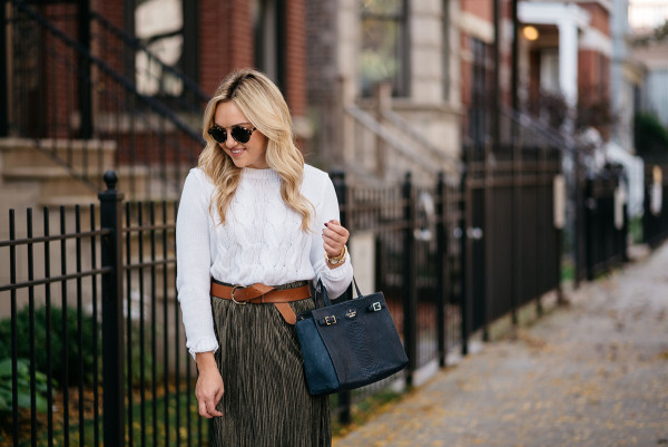 Bows & Sequins wearing a cable knit sweater, leather belt, Kate Spade bag, and pleated metallic skirt.
