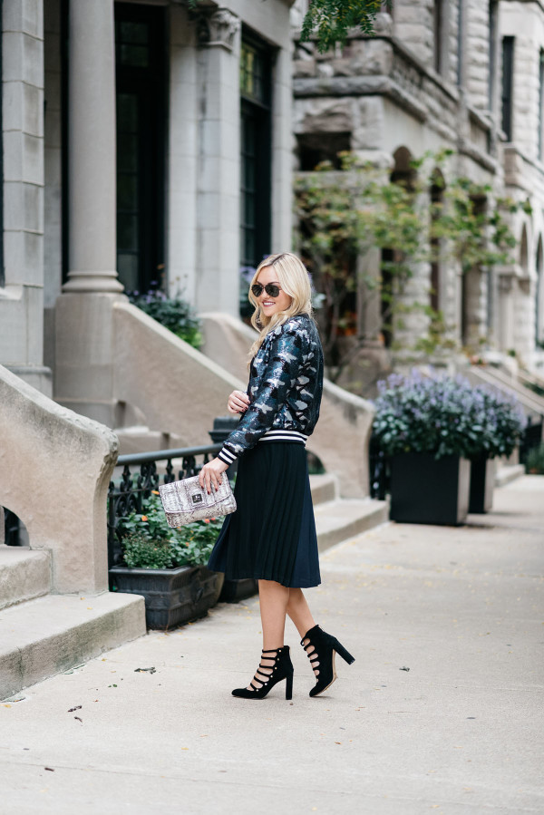 Bows & Sequins styling a sequin bomber jacket, crop top, pleated midi skirt, and military-inspired pumps for fall.