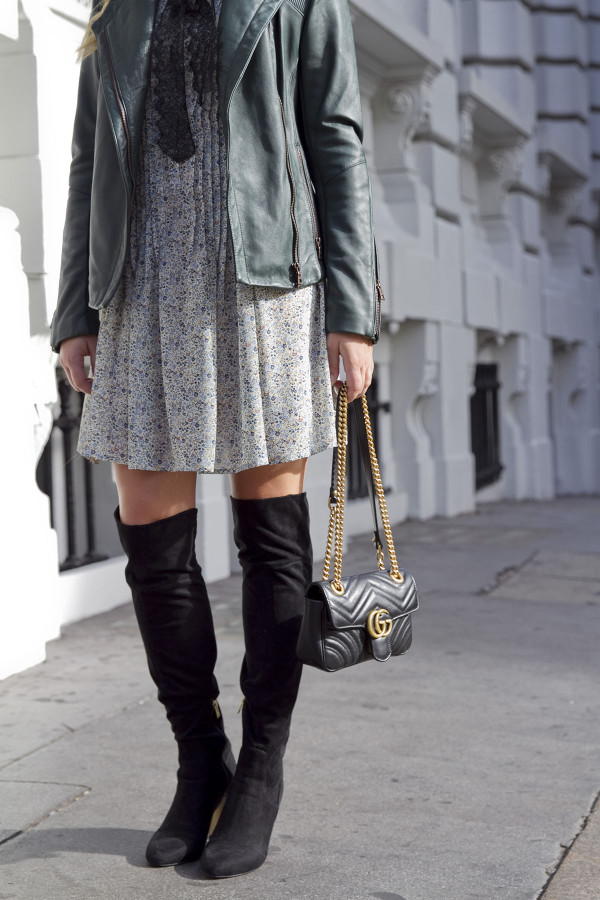Bows & Sequins wearing a floral dress for fall, styled with over the knee boots, a leather jacket, and a Gucci chain strap bag.