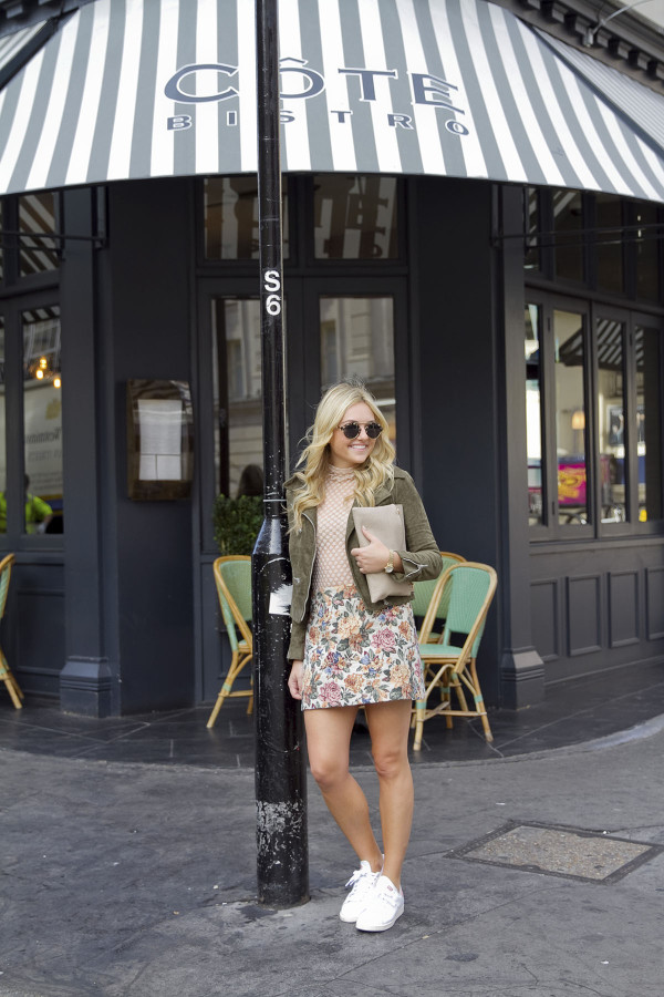 Fashion blogger Jessica Sturdy styling a fall outfit in London during Fashion Week! Outfit Details: Olive Green Suede Moto Jacket, Sheer Mock-Neck Top, Zara Floral Tapestry Skirt, White and Blush Pink Adidas Stan Smith Sneakers, Illesteva Sunglasses, and an Envelope Clutch