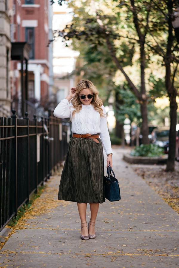 Bows & Sequins styling a pleated metallic skirt for a fall with a white cable knit sweater, a leather belt, a navy handbag, and Kate Spade glitter heels.