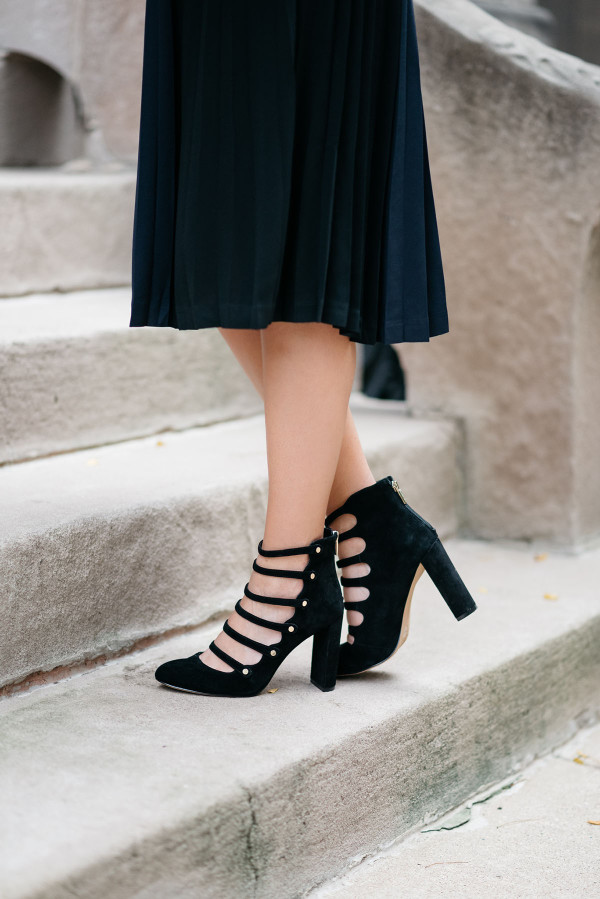 Bows & Sequins styling a pleated midi skirt and military inspired pumps.