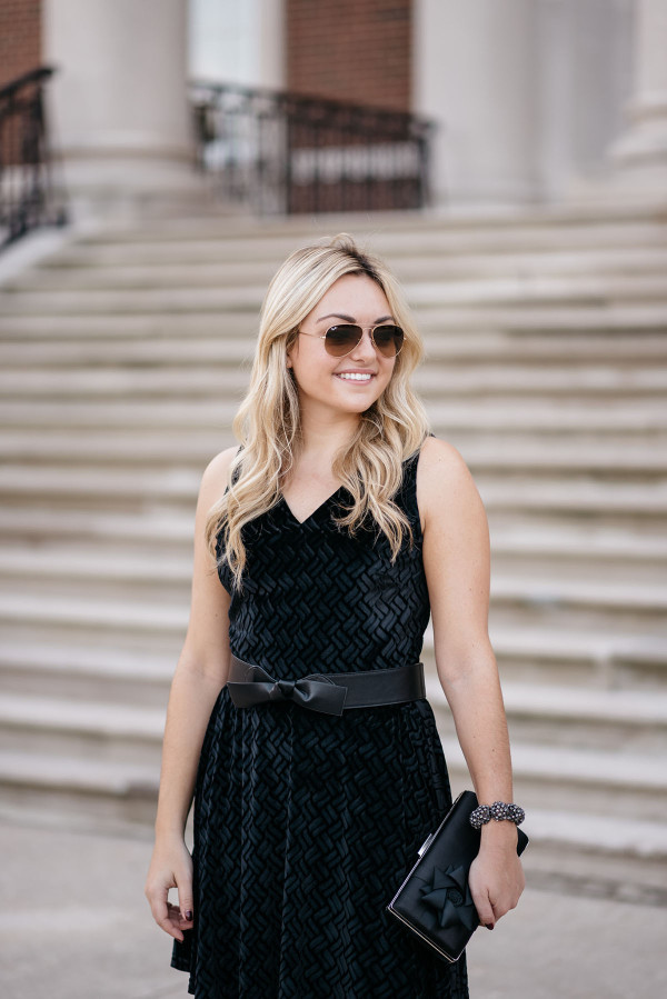Bows & Sequins styling a sleeveless velvet dress with a black bow belt.