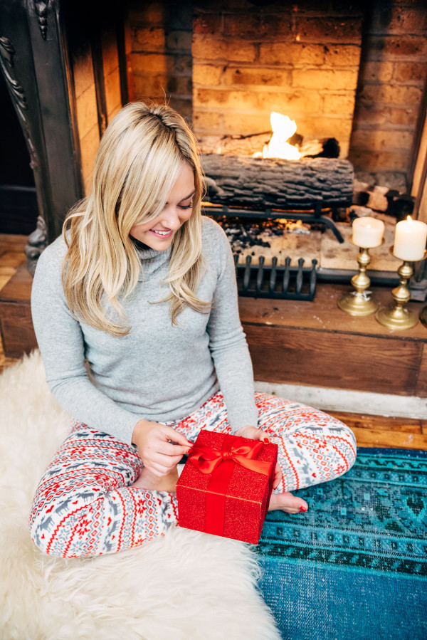 Bows & Sequins opening presents by the fireplace in Christmas PJs.
