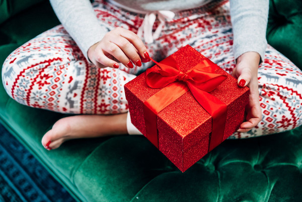 Bows & Sequins opening a red glitter present in Christmas pajamas on a tufted green velvet sofa.