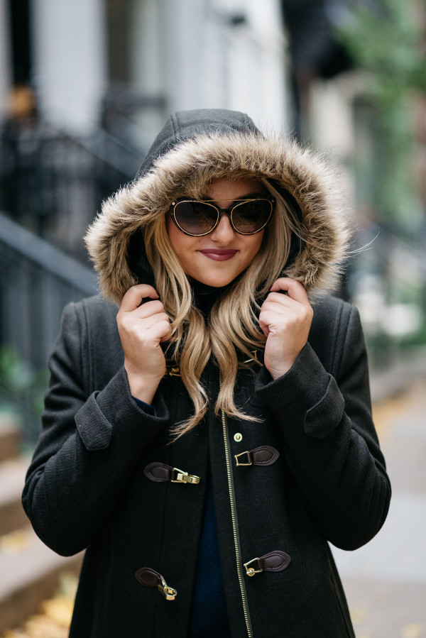 Bows & Sequins wearing a fur-trimmed Cole Haan coat and Tom Ford sunglasses.