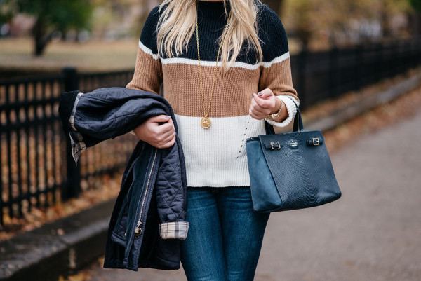 Bows & Sequins wearing a casual outfit for Thanksgiving: a striped, mockneck sweater, dark denim, a simple pendant necklace, a navy blue Kate Spade bag, and a quilted Barbour jacket.