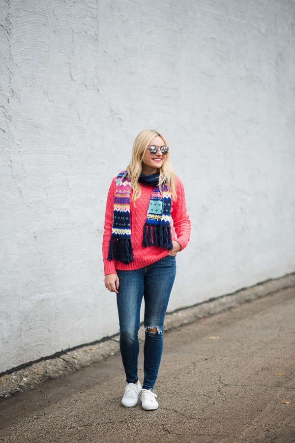 Bows & Sequins wearing a neon pink sweater with a fair isle scarf, blue jeans, silver mirrored sunglasses, and white sneakers
