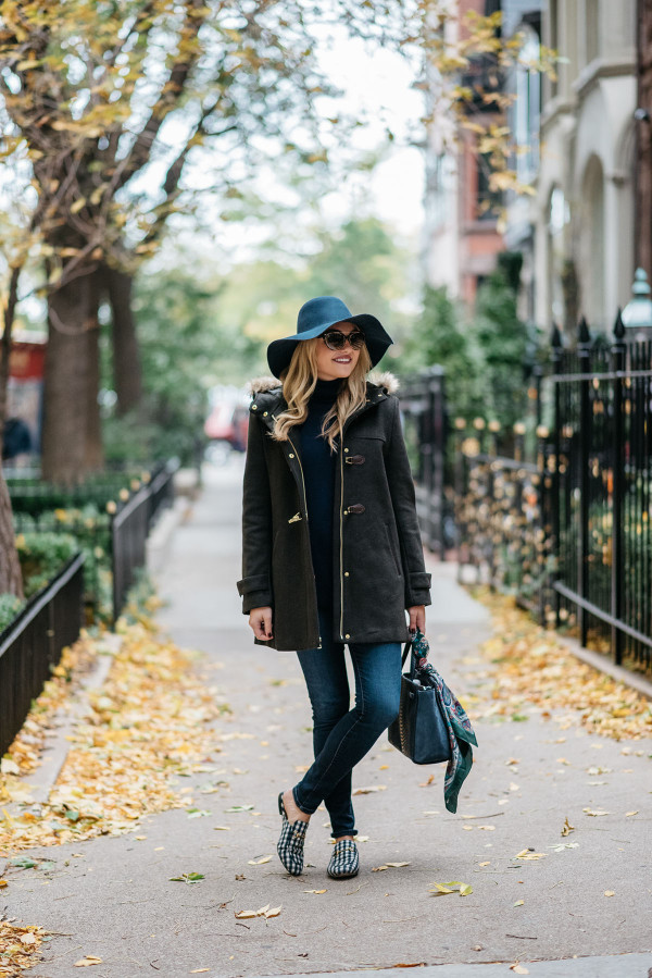 Bows & Sequins styling a fall outfit: floppy hat, dark green toggle coat, Rag & Bone skinny jeans, Gucci loafers, Tom Ford sunglasses, and a Kate Spade bag.