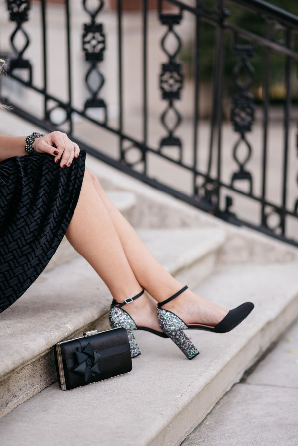 Bows & Sequins wearing black and silver glitter heel pumps with an ankle strap.
