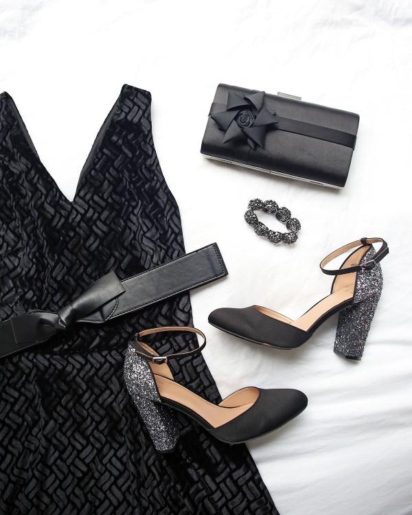 Black velvet dress, leather bow belt, glitter heel pumps, and a black bow clutch.