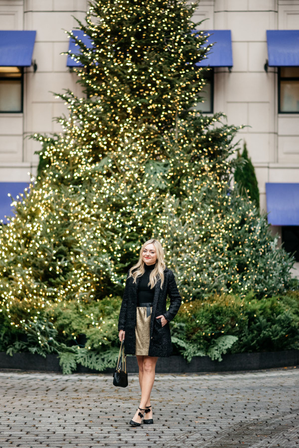Bows & Sequins styling a black and gold holiday outfit: Sail to Sable sparkly tweed jacket, a black turtleneck, a gold tweed skirt with a bow belt, a Gucci Marmont bag, and Kate Spade glitter pom-pom heels! Photo taken in front of the Christmas Tree at the Waldorf Astoria in Chicago's Gold Coast.
