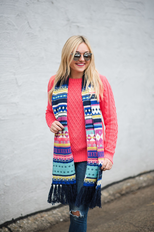 Bows & Sequins wearing a neon pink sweater with a fair isle scarf, blue jeans, and silver mirrored sunglasses.