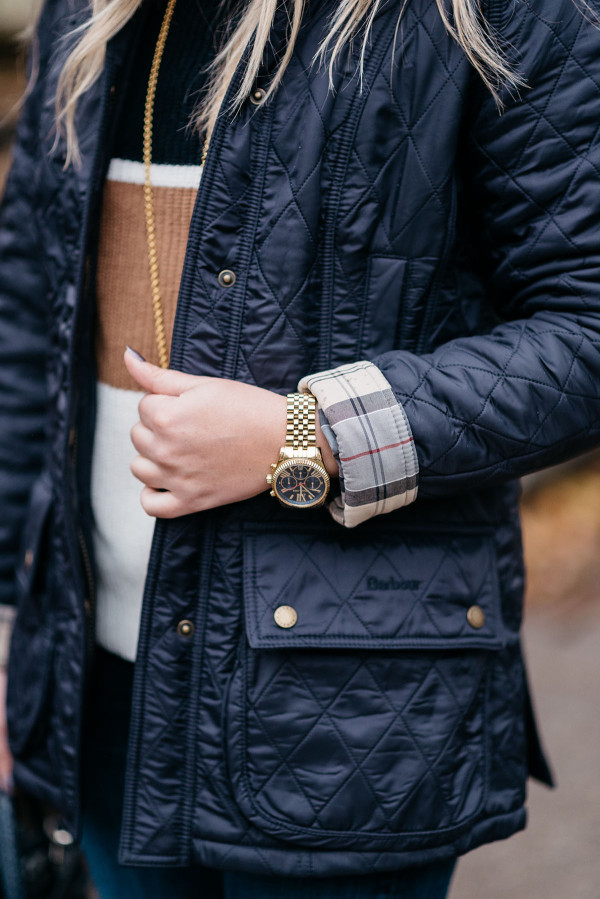 Bows & Sequins wearing a quilted navy Barbour Beadnell PolarQuilt jacket with plaid lining.