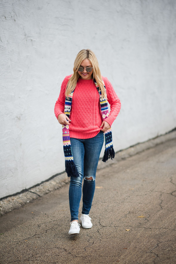 Bows & Sequins wearing a neon pink sweater with a fair isle scarf, blue jeans, and white sneakers