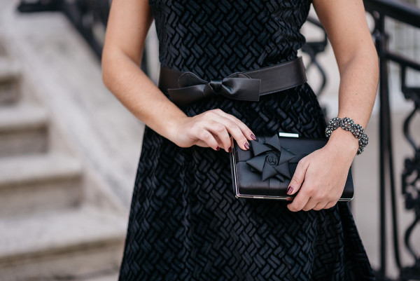 A black velvet fit & flare dress worn with a leather bow belt and a bow box clutch.